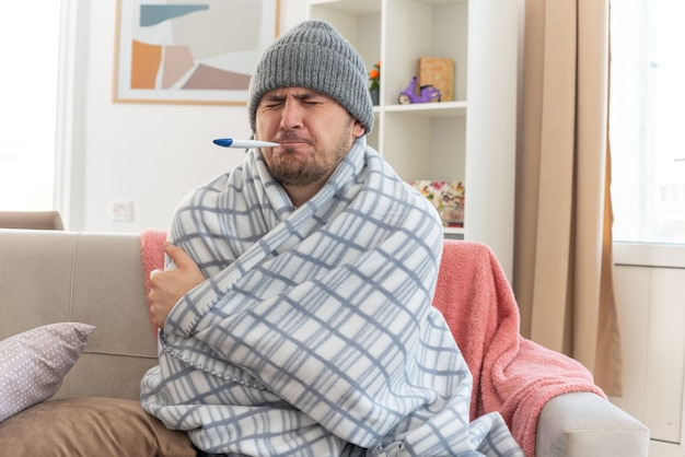 Schmerzender kranker slawischer mann mit schal um den hals, der eine in plaid gewickelte wintermütze trägt, die seine temperatur mit einem thermometer auf der couch im wohnzimmer misst