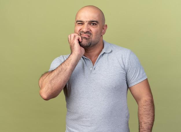 Schmerzender lässiger mann mittleren alters, der die hand auf der wange hält und an zahnschmerzen leidet, isoliert auf olivgrüner wand?