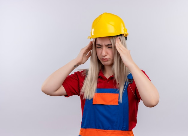 Schmerzendes junges blondes ingenieur-baumeistermädchen in der uniform, die kopfschmerzen hat, die hände auf schläfen mit geschlossenen augen auf isoliertem weißem raum mit kopienraum setzen