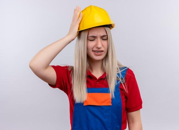 Schmerzendes junges blondes ingenieur-baumeistermädchen in uniform in zahnspangen, die hand auf kopf setzen, der kopfschmerzen mit geschlossenen augen auf isoliertem weißen raum hat