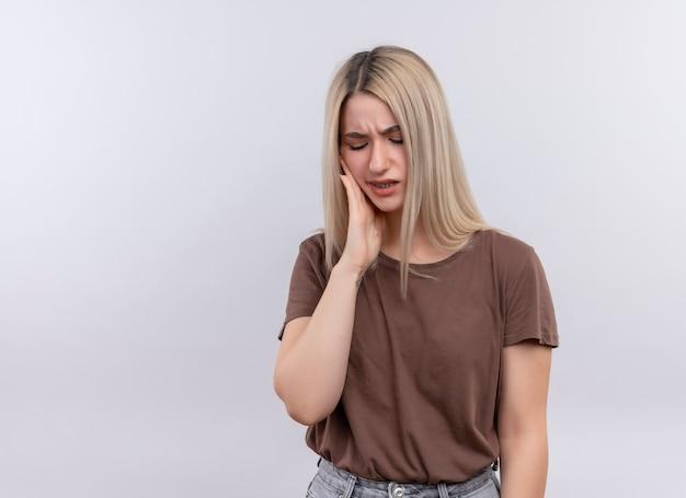 Schmerzendes junges blondes mädchen, das hand auf wange legt, die zahnschmerzen auf lokalisiertem leerraum mit kopienraum hat