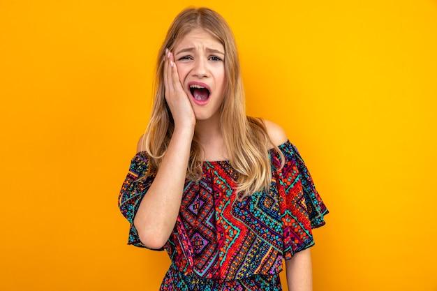 Schmerzendes junges blondes slawisches mädchen, das sich die hand aufs gesicht legt