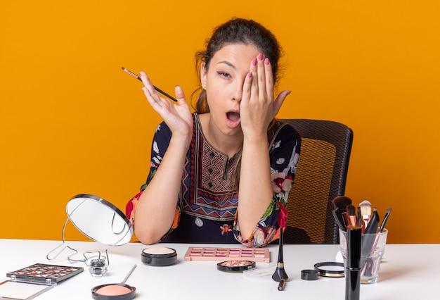 Schmerzendes junges brünettes mädchen, das am tisch mit make-up-tools sitzt, die hand auf ihr auge legt und make-up-pinsel isoliert auf oranger wand mit kopierraum hält
