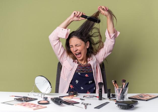 Schmerzendes junges brünettes mädchen, das am tisch mit make-up-tools sitzt und ihr haar hält und kämmt