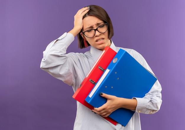 Schmerzendes junges callcenter-mädchen, das eine brille trägt, die ordner hält, die hand auf kopf mit geschlossenen augen setzen, die unter kopfschmerzen leiden, die auf purpur isoliert werden