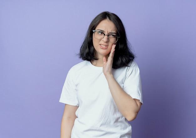 Schmerzendes junges hübsches kaukasisches mädchen, das eine brille trägt, die hand auf die wange setzt, die seite betrachtet, die unter zahnschmerzen leidet, lokalisiert auf lila hintergrund mit kopienraum