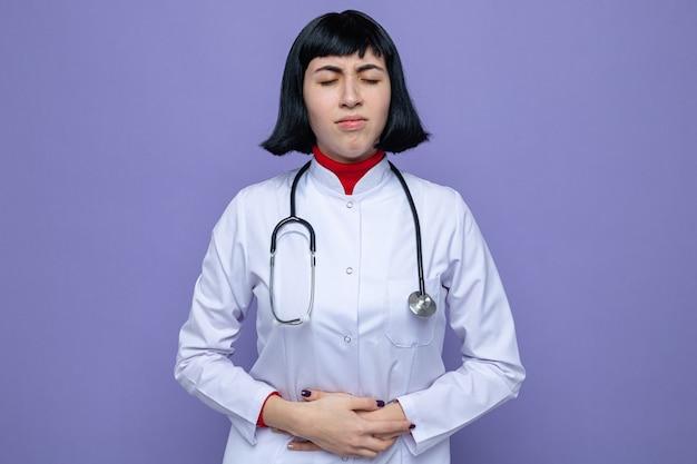 Schmerzendes junges hübsches kaukasisches mädchen in arztuniform mit stethoskop, das die hände auf den bauch legt