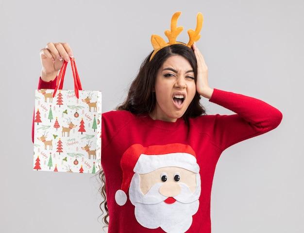 Schmerzendes junges hübsches mädchen, das rentiergeweih-stirnband und weihnachtsmann-pullover hält, der weihnachtsgeschenkbeutel hält, der kamera betrachtet, die hand auf kopf hält, der kopfschmerz lokalisiert auf weißem hintergrund hat