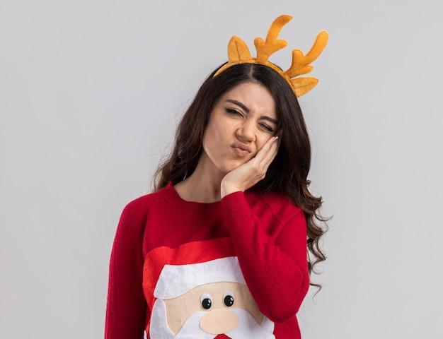 Schmerzendes junges hübsches mädchen, das rentiergeweih-stirnband und weihnachtsmannpullover trägt, der hand auf gesicht hält, das zahnschmerzen hat, die mit einem geschlossenen auge schauen