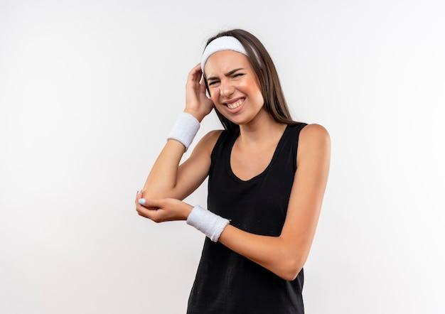 Schmerzendes junges hübsches sportliches mädchen mit stirnband und armband, das die hände auf den arm und den kopf auf die weiße wand legt