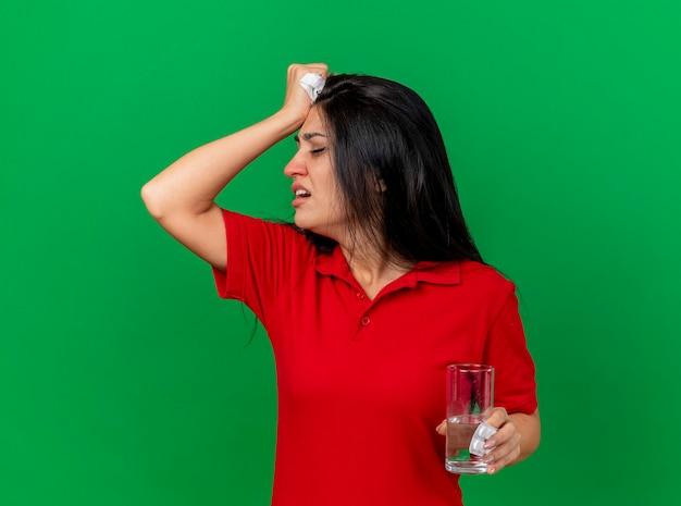 Schmerzendes junges kaukasisches krankes mädchen, das packung tablettenglas wasser und serviette hält, die kopf zur seite dreht, die hand auf kopf hält, die unter kopfschmerzen lokalisiert auf grünem hintergrund mit kopienraum leidet