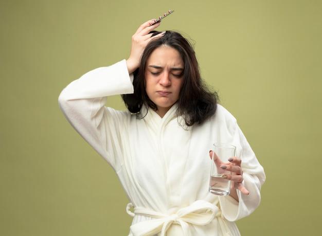 Schmerzendes junges kaukasisches krankes mädchen, das robe hält glas des wassers und packung der medizinischen pillen, die kopf mit geschlossenen augen berühren, lokalisiert auf olivgrünem hintergrund