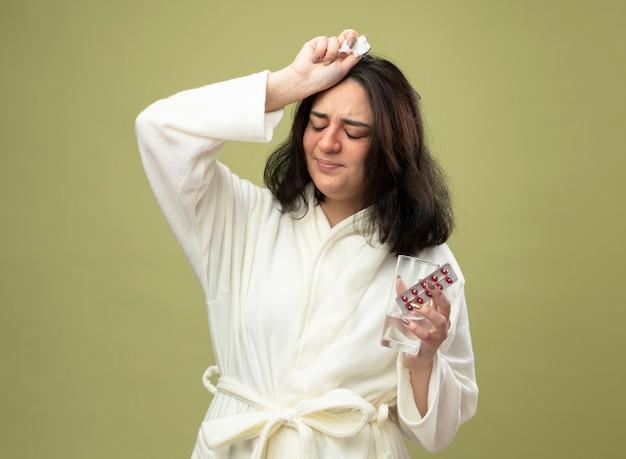 Schmerzendes junges kaukasisches krankes mädchen, das robe hält packung der medizinischen pillen glas wasser und serviette berührt kopf mit geschlossenen augen lokalisiert auf olivgrünem hintergrund mit kopienraum