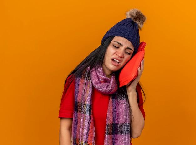 Schmerzendes junges kaukasisches krankes mädchen, das wintermütze und schal berührendes gesicht mit heißem wassersack mit geschlossenen augen trägt, die auf orange wand mit kopienraum lokalisiert werden