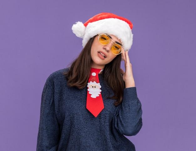 Schmerzendes junges kaukasisches mädchen in sonnenbrille mit weihnachtsmütze und weihnachtsmann-krawatte legt die hand auf ihren tempel, isoliert auf lila wand mit kopierraum