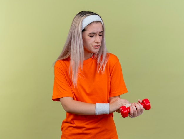 Schmerzendes junges kaukasisches sportliches mädchen mit hosenträgern, das stirnband und armbänder trägt, hält hantel und sieht zur hand