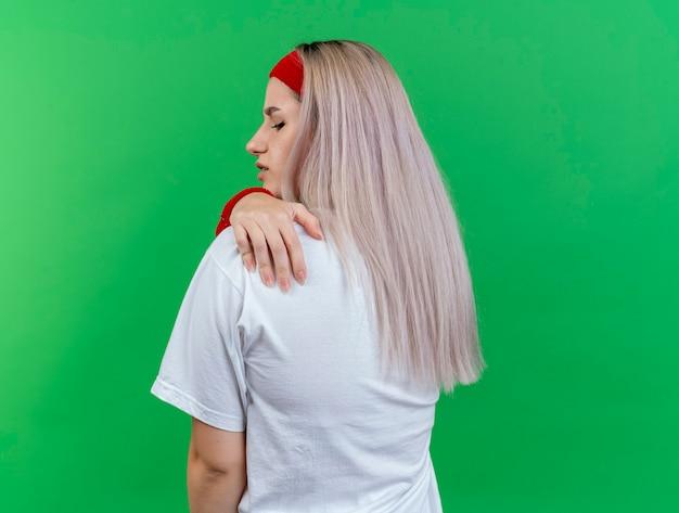 Schmerzendes junges kaukasisches sportliches mädchen mit hosenträgern, das stirnband und armbänder trägt, steht mit dem rücken zur kamera, die hand auf die schulter legt