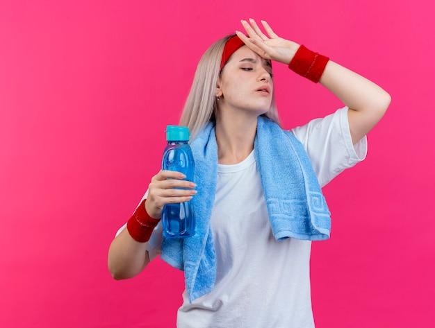 Schmerzendes junges kaukasisches sportliches mädchen mit hosenträgern und mit handtuch am hals, das stirnband und armbänder trägt, legt die hand auf die stirn und hält eine wasserflasche