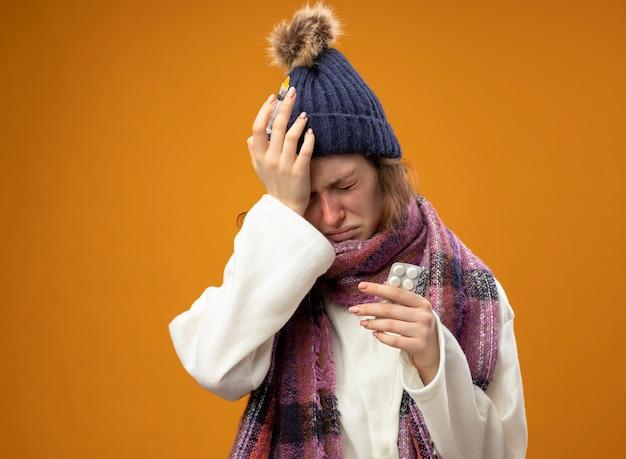 Schmerzendes junges krankes mädchen, das weiße robe und wintermütze mit schal hält spritze mit pillen trägt hand auf stirn lokalisiert auf orange hält