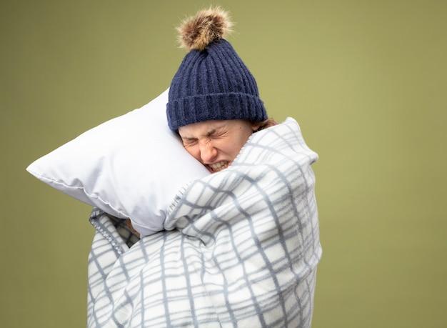 Schmerzendes junges krankes mädchen, das weiße robe und wintermütze mit schal wickelt, der im karierten umarmten kissen eingewickelt wird