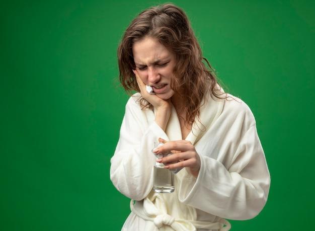 Schmerzendes junges krankes mädchen, das weißes gewand hält glas des wassers hält hand auf wange lokalisiert auf grün