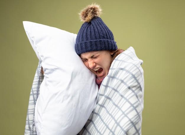 Schmerzendes junges krankes mädchen mit geschlossenen augen, die weiße robe und wintermütze mit schal tragen, der in kariertes umarmtes kissen gewickelt wird