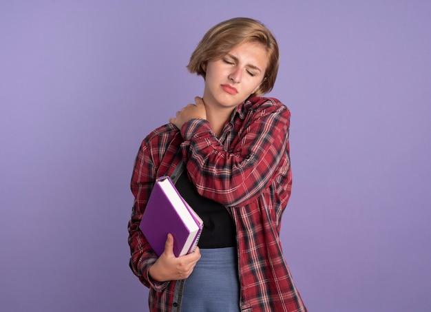 Schmerzendes junges slawisches studentenmädchen legt hand auf schulter hält buch und notizbuch