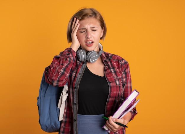 Schmerzendes junges slawisches studentenmädchen mit kopfhörern, das rucksack trägt, legt die hand auf den kopf, hält buch und notizbuch