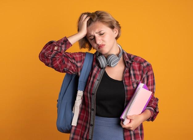Schmerzendes junges slawisches studentenmädchen mit kopfhörern, das rucksack trägt, legt hand auf die stirn, hält buch und notizbuch