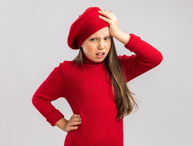Schmerzendes kleines blondes mädchen mit rotem barett, das die hand auf dem kopf und auf dem bauch hält, isoliert auf weißer wand mit kopierraum