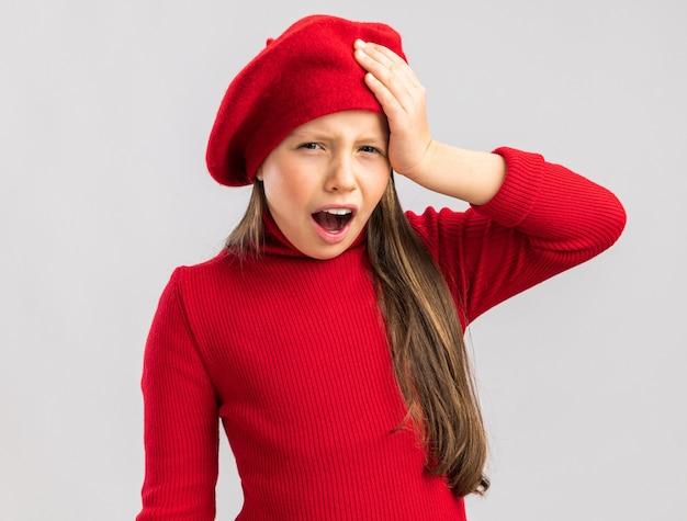 Schmerzendes kleines blondes mädchen mit rotem barett, das die hand mit offenem mund auf den kopf hält und die kamera isoliert auf weißer wand betrachtet