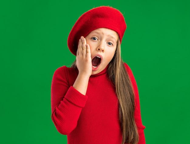 Schmerzendes kleines blondes mädchen mit rotem barett, das nach vorne schaut und die hand am kinn mit offenem mund hält, isoliert auf grüner wand mit kopierraum