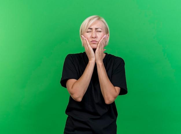 Schmerzhafte blonde slawische frau mittleren alters, die hände auf wangen legt, die unter zahnschmerzen mit geschlossenen augen leiden, lokalisiert auf grüner wand mit kopienraum