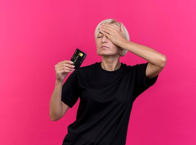 Schmerzhafte blonde slawische frau mittleren alters, die kreditkarte hält, die hand auf kopf mit geschlossenen augen hält, lokalisiert auf rosa wand mit kopienraum