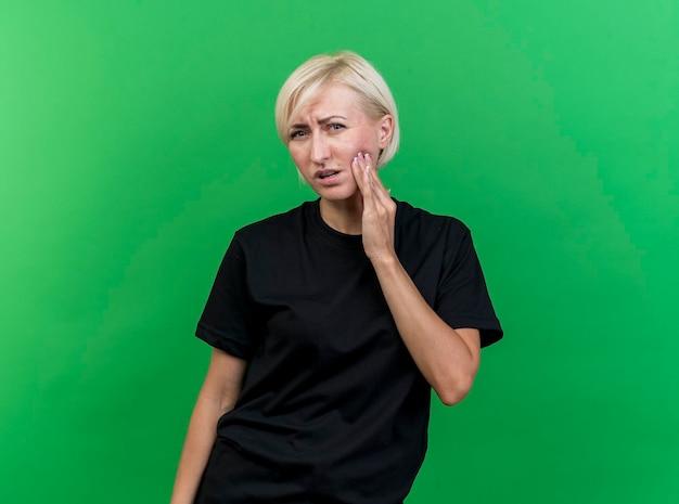 Schmerzhafte blonde slawische frau mittleren alters, die nach vorne schaut und hand auf die wange legt, die unter zahnschmerzen leidet, lokalisiert auf grüner wand mit kopienraum