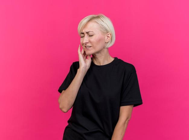 Schmerzhafte blonde slawische frau mittleren alters, die wange berührt, die unter kopfschmerzen mit geschlossenen augen leidet, lokalisiert auf rosa wand mit kopienraum