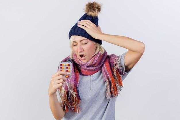 Schmerzhafte junge blonde kranke slawische frau, die wintermütze und schal trägt, legt hand auf kopf und hält packung der medizinischen pillen lokalisiert auf weißer wand mit kopienraum