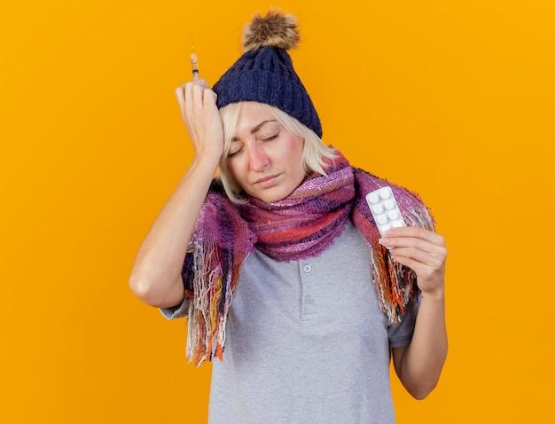 Schmerzhafte junge blonde kranke slawische frau, die wintermütze und schal trägt, setzt hand auf kopf, der spritze und packung der medizinischen pillen hält, die auf orange wand mit kopienraum isoliert werden