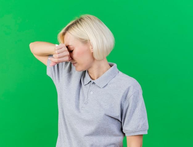 Schmerzhafte junge blonde kranke slawische frau legt hand auf gesicht, das gewebe lokalisiert auf grüner wand mit kopienraum hält