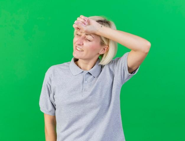 Schmerzhafte junge blonde kranke slawische frau legt hand auf stirn lokalisiert auf grün
