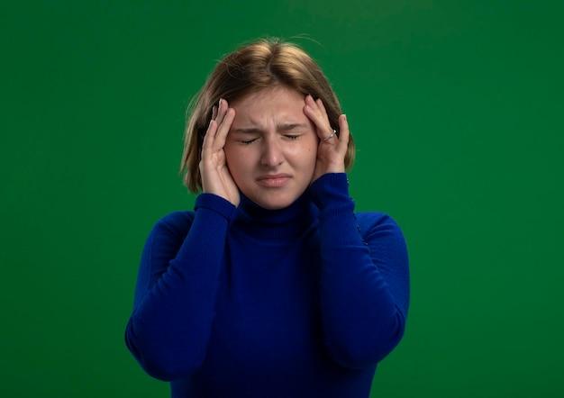 Schmerzhafte junge blonde superheldenfrau, die hände auf kopf mit geschlossenen augen lokalisiert auf grüner wand mit kopienraum hält