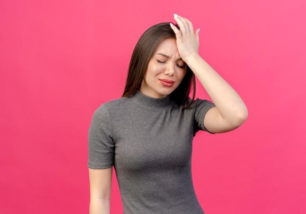 Schmerzhafte junge hübsche frau, die hand auf kopf setzt, der unter kopfschmerzen mit geschlossenen augen leidet, lokalisiert auf rosa hintergrund mit kopienraum