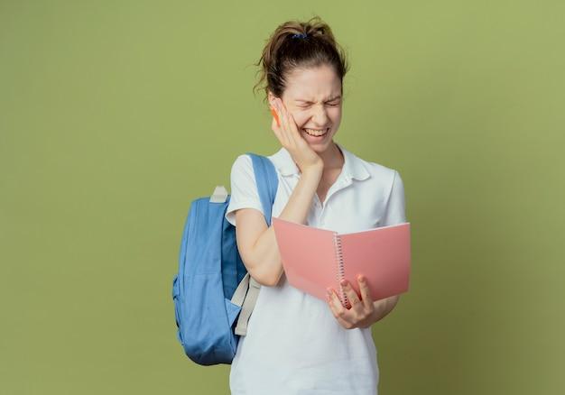 Schmerzhafte junge hübsche studentin, die rückentasche hält stift und offenen notizblock, der hand auf wange leidet, die unter zahnschmerzen mit geschlossenen augen leidet, lokalisiert auf grünem hintergrund mit kopienraum