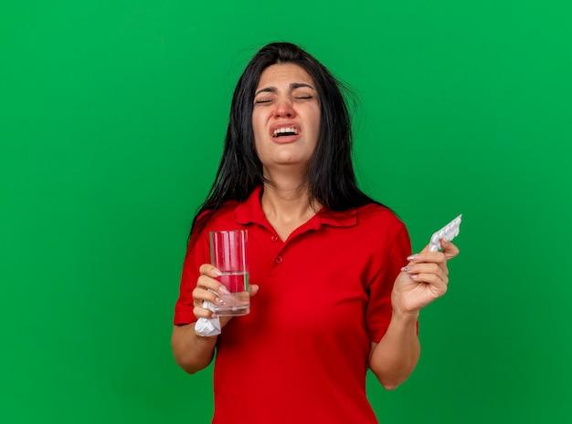Schmerzhafte junge kranke frau, die packung tablettenglas wasser und serviette mit geschlossenen augen lokalisiert auf grüner wand hält
