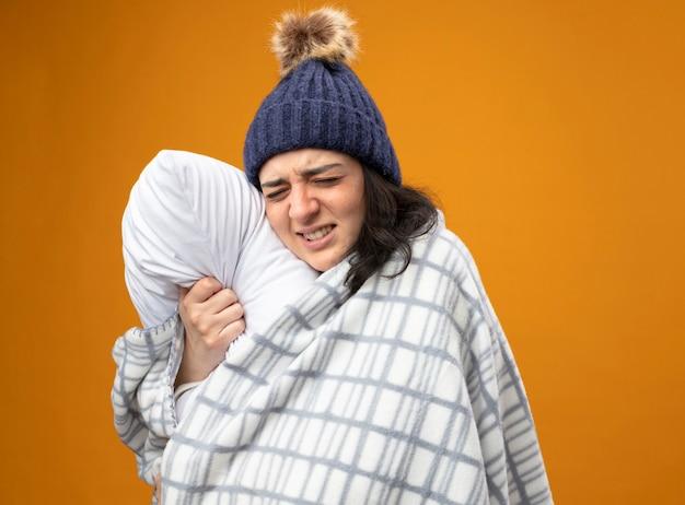 Schmerzhafte junge kranke frau, die robe wintermütze in plaid gewickelt steht in profilansicht umarmendes kissen mit geschlossenen augen auf orange wand isoliert