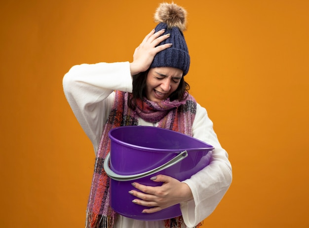 Schmerzhafte junge kranke frau, die robe wintermütze und schal hält plastikeimer mit übelkeit hält hand auf kopf mit geschlossenen augen isoliert auf orange wand