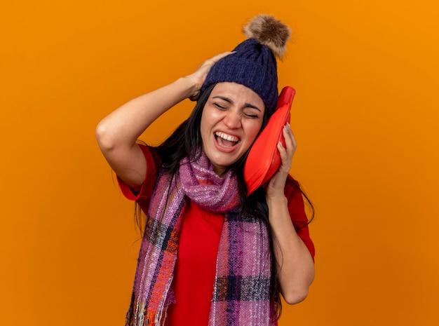 Schmerzhafte junge kranke frau, die wintermütze und schal berührendes gesicht mit heißwassersack trägt, hält hand auf kopf mit geschlossenen augen lokalisiert auf orange wand