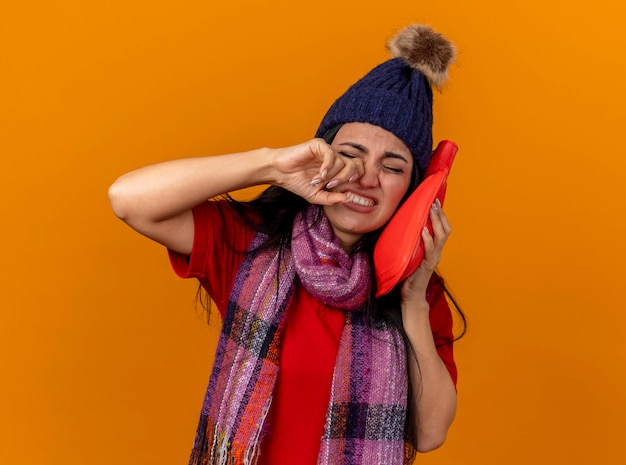 Schmerzhafte junge kranke frau, die wintermütze und schal berührt gesicht mit heißem wasserbeutel berührt nase mit geschlossenen augen auf orange wand isoliert