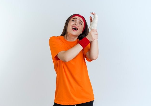 Schmerzhafte junge sportliche frau, die stirnband und armbänder trägt, die verletztes handgelenk halten, eingewickelt in verband, der lokal oben schaut
