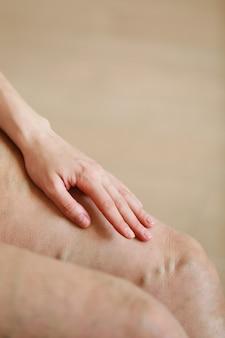Schmerzhafte krampfadern und besenreiser an den beinen der aktiven frau, die sich selbst helfen, den schmerz zu überwinden. gefäßerkrankungen, krampfadernprobleme, aktives lebenskonzept.